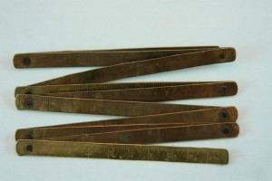 A vintage metal folding ruler with 10 arms.