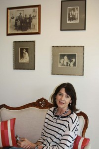 Susie sitting on a french walnut sofa under photos of Maddie and Marie and their families.